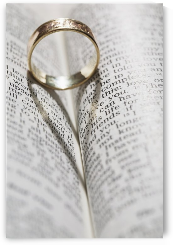 Close up of a gold ring with the shadow of an heart on book about love;Calgary Alberta Canada by PacificStock