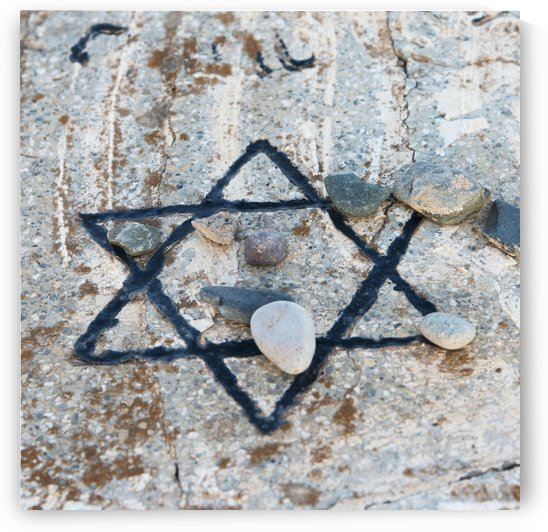 A star of david etched and painted on a rock with stones laying on it by PacificStock