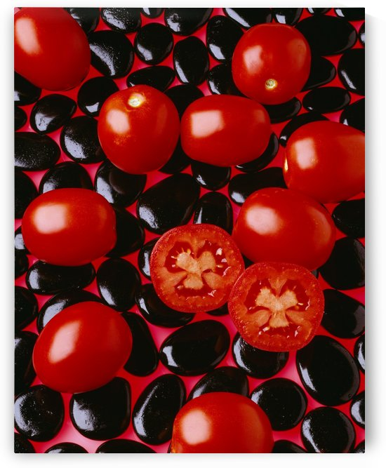 Agriculture - Processing tomatoes on black rocks and red surface, sliced, studio. by PacificStock