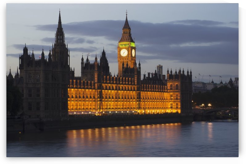 A Building And Clock Tower Along The Water's Edge Illuminated At Dusk; London, England by PacificStock