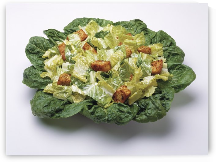 Food - Caesar salad prepared with Romaine lettuce, dressing, parmesan cheese and croutons, studio. by PacificStock