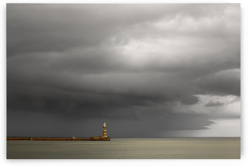 Lighthouse at the end of a pier with dark storm clouds overhead; Sunderland, Tyne and Wear, England by PacificStock