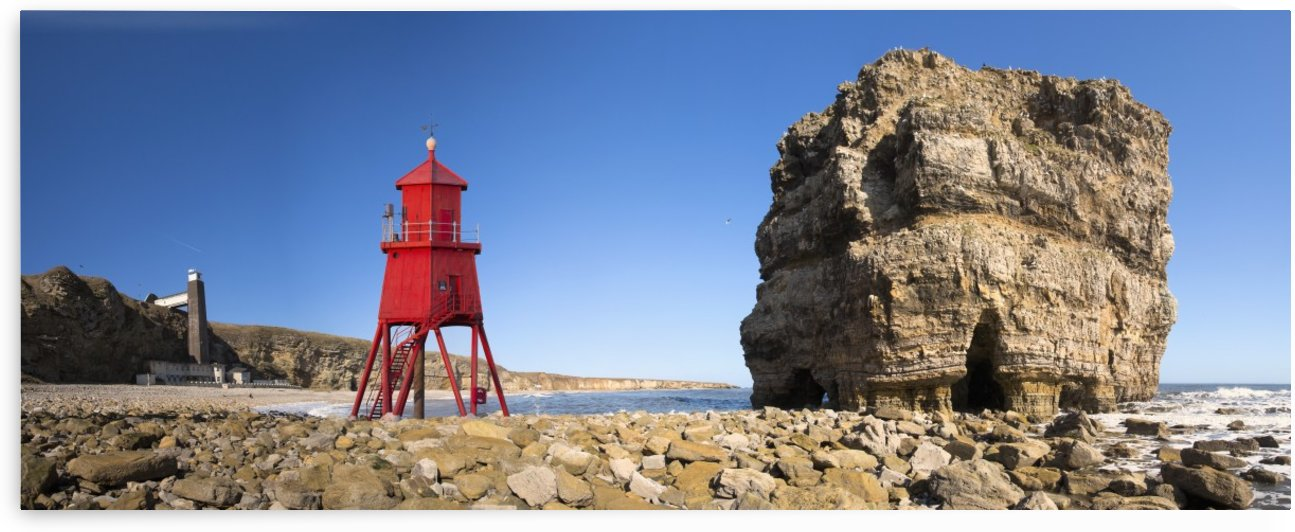 Groyne lighthouse beside a rock formation along the shoreline; South Shields, Tyne and Wear, England by PacificStock