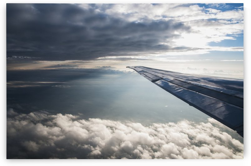 A commercial jet flies through the clouds; Colorado, United States of America by PacificStock