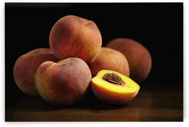 Peaches sitting on a wooden table, one cut in half; Montreal, Quebec, Canada by PacificStock