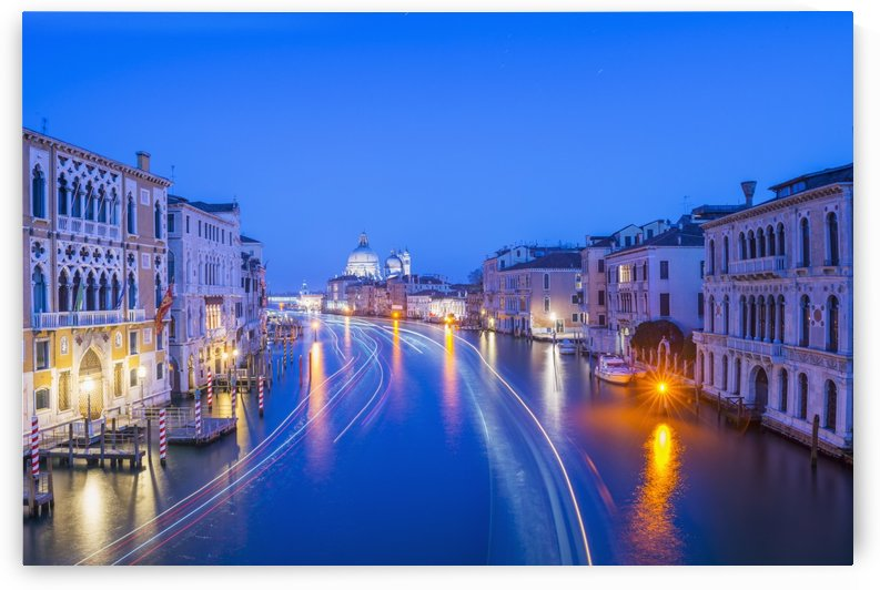 Light trails on a canal at dusk with the illuminated Salute church in the distance; Venice, Veneto, Italy by PacificStock
