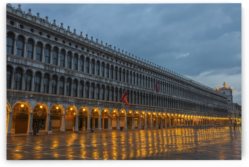 Lighted archways in a row along a building reflected in the wet pavement, Piazza san marco; Venice, Veneto, Italy by PacificStock