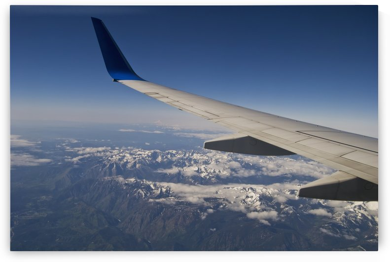 A commercial jet flies over the mountains of the American West; Colorado, United States of America by PacificStock