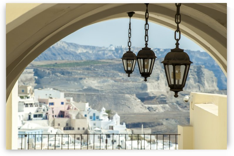 Lights hang from an arched ceiling with a view of a church, whitewashed buildings and landscape; Fira, Santorini, Greece by PacificStock