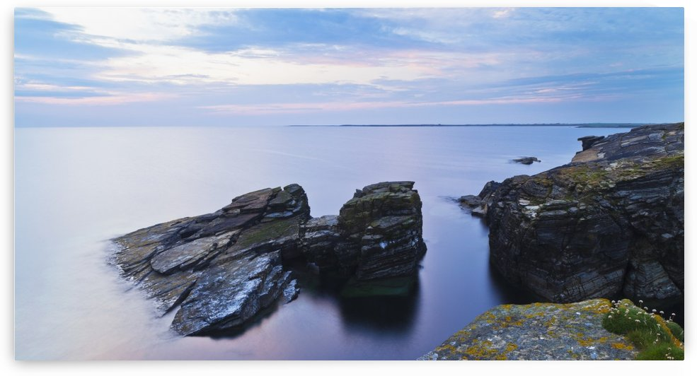 Rock and tranquil water along the coastline at dawn; Orkney, Scotland by PacificStock