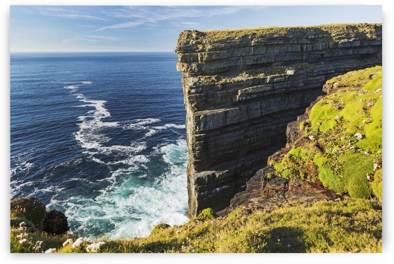 Cliff face rock formation in ocean with waves, blue sky and clouds; Kilkee, County Clare, Ireland by PacificStock