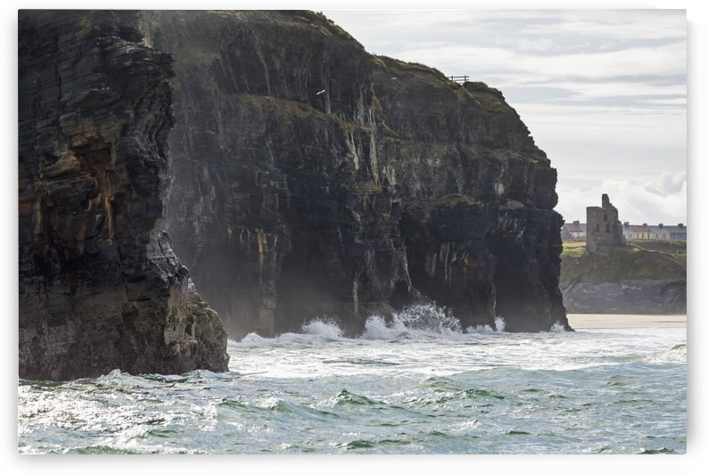 Dark straight cliffs with waves crashing into the rock with ruined castle turret in background; Ballybunion, County Kerry, Ireland by PacificStock