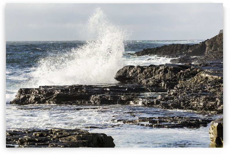 Wave crashing into rocky coast with cloudy sky; Kilkee, County Clare, Ireland by PacificStock