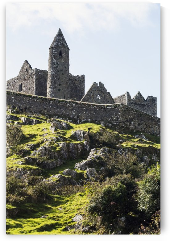 Ancient stone ruin with stone wall, turret and church on rocky grassy hillside with blue sky and clouds; Cashel, County Tipperary, Ireland by PacificStock