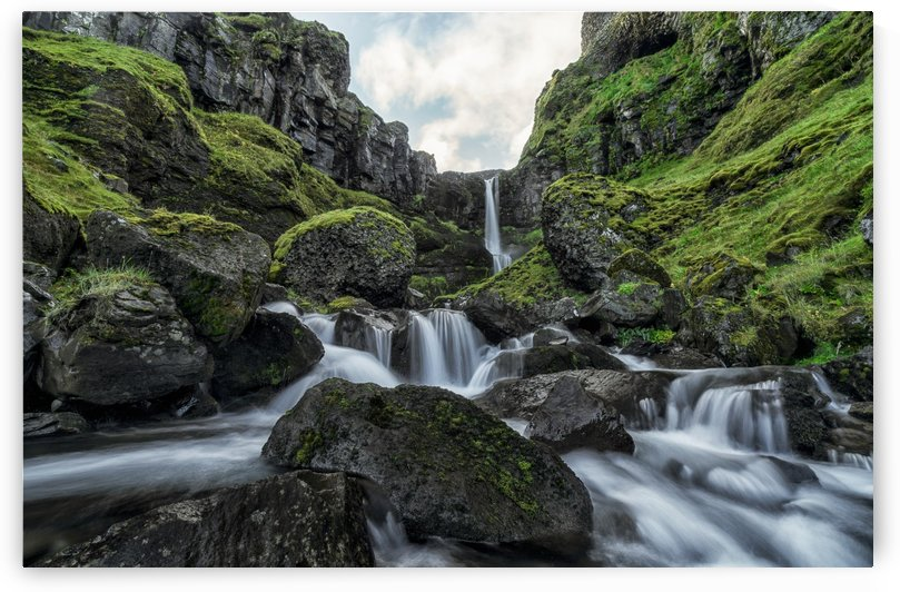 An unnamed stream flows over a cliff face creating a beautiful waterfall after a period of heavy rains; Iceland by PacificStock
