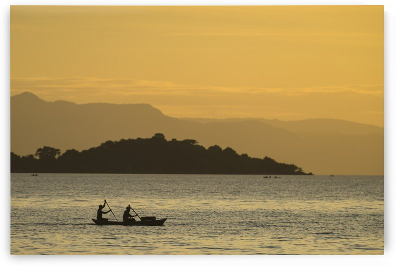 Silhouette of fishermen in dugout canoe leaving Cape Maclear in the evening, Lake Malawi; Malawi by PacificStock