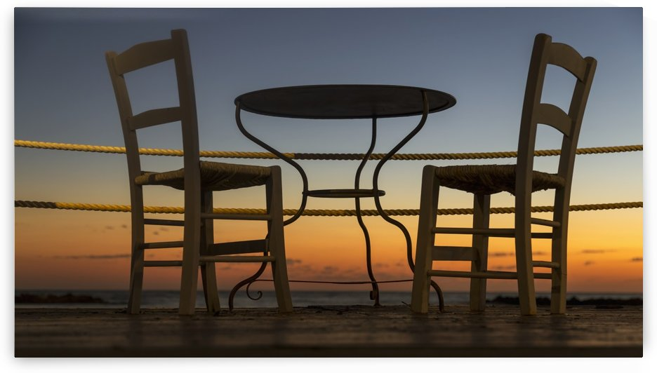 A table and chairs on a patio with a view of a colourful sunset; Paphos, Cyprus by PacificStock