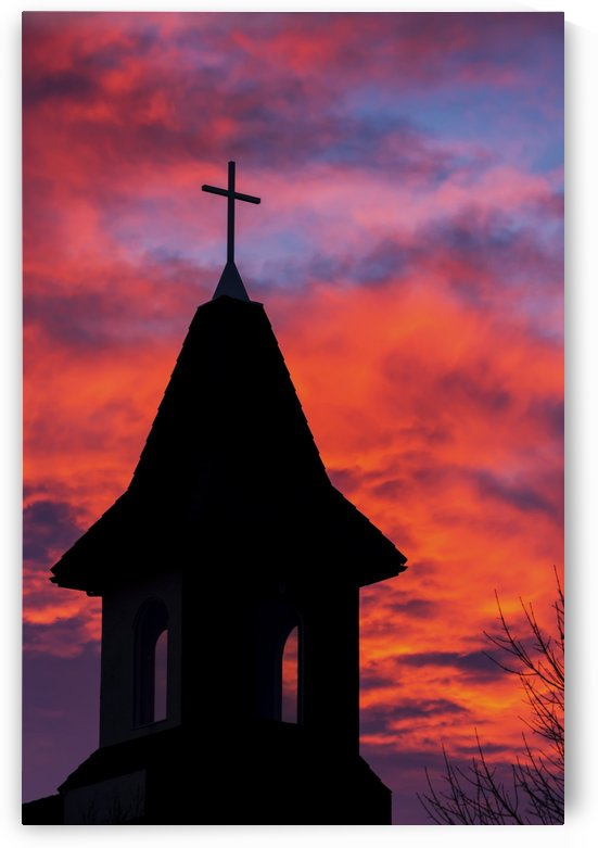 Silhouette of a church steeple with colourful clouds and blue sky in the background; Calgary, Alberta, Canada by PacificStock
