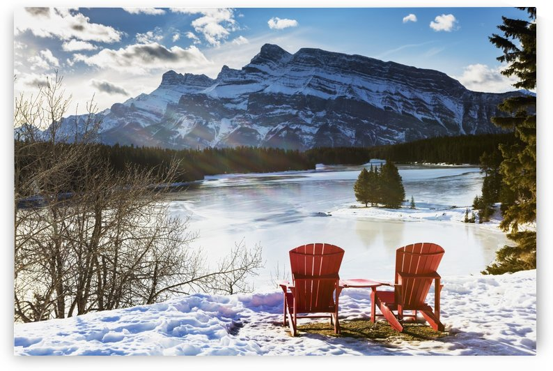 Two red chairs on snow covered ridge overlooking frozen lake with snow covered mountain in the background with blue sky and clouds; Banff, Alberta, Canada by PacificStock
