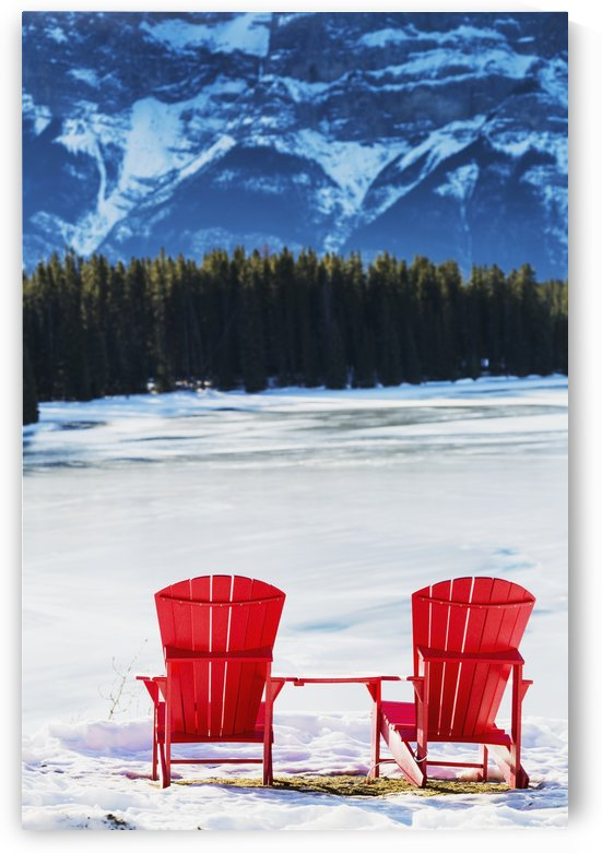 Two red chairs on snow covered ridge overlooking frozen lake with snow covered mountain cliff in the background; Banff, Alberta, Canada by PacificStock