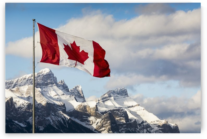 Canadian flag blowing in the wind on a flag pole with snow covered mountain range in the background with blue sky and clouds; Canmore, Alberta, Canada by PacificStock