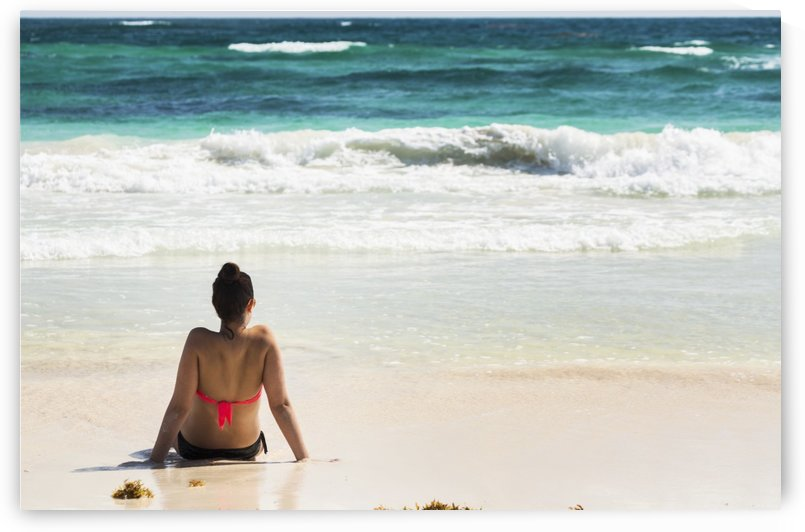 Young woman sitting on sandy beach in water looking out at waves coming in and blue sky; Akumal, Quintana Roo, Mexico by PacificStock