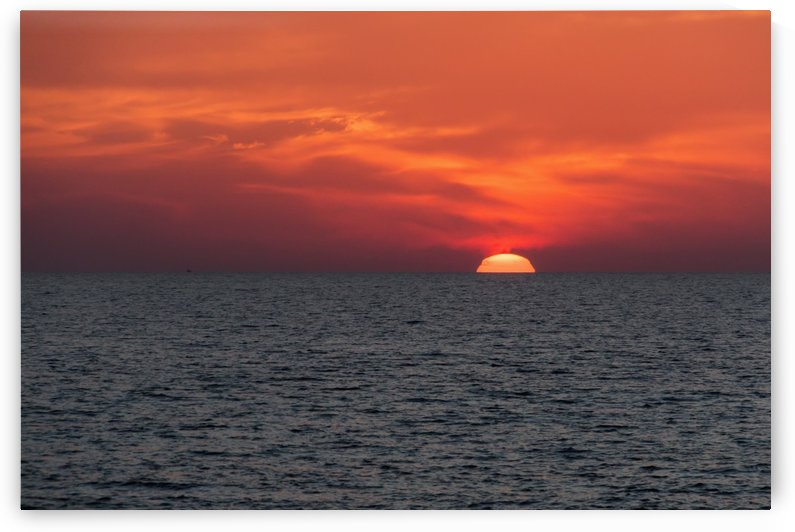 Dramatic red sky with the sun setting under the ocean and horizon; Paphos, Cyprus by PacificStock