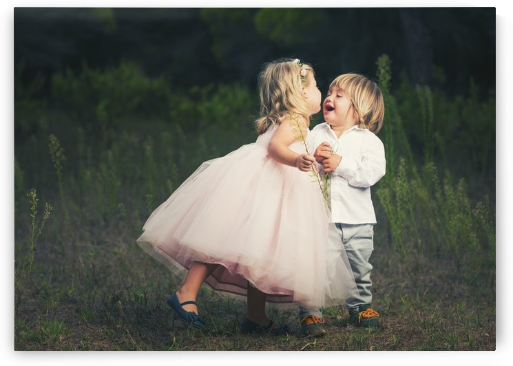 A young girl with a pink princess dress leans in to kiss a young boy; Tarifa, Cadiz, Andalusia, Spain by PacificStock