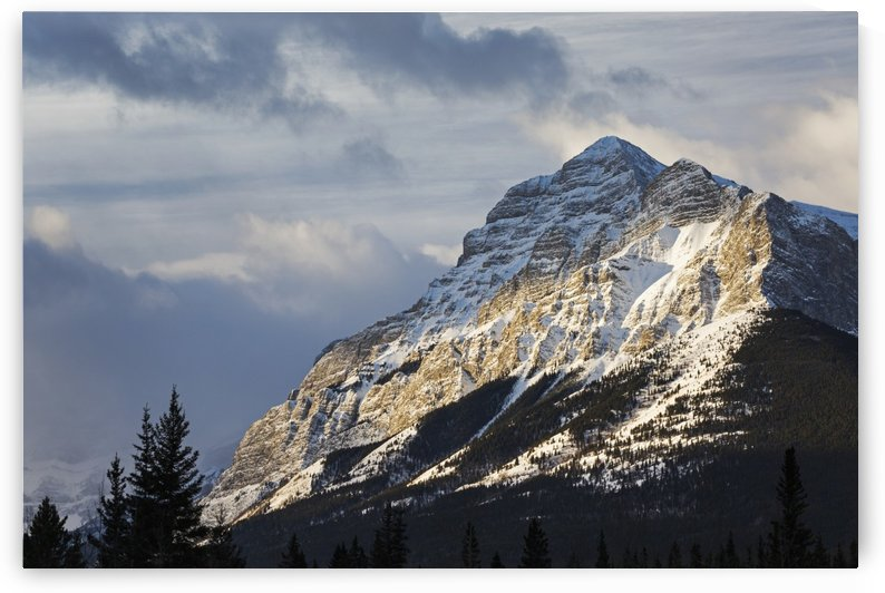 Sun breaking through the clouds partially lighting a snow covered mountain with clouds in the sky; Kananaskis Country, Alberta, Canada by PacificStock