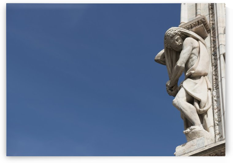 Carved sculpture of male likeness on the facade of Milan Cathedral against a blue sky; Milan, Lombardy, Italy by PacificStock