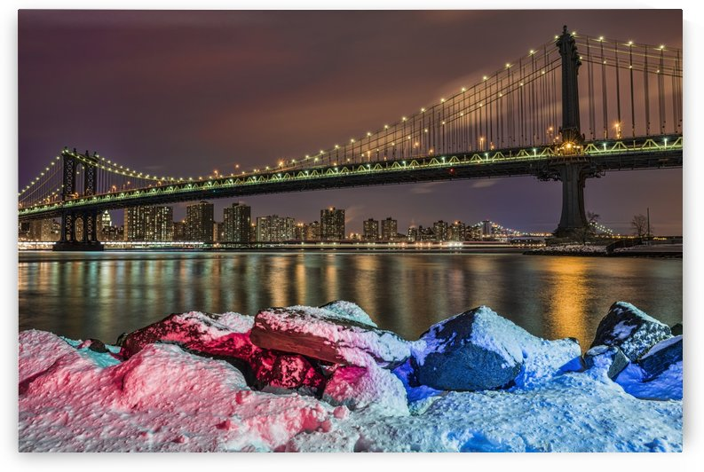 Manhattan Bridge by snow-covered rocks at sunset, Brooklyn Bridge Park; Brooklyn, New York, United States of America by PacificStock