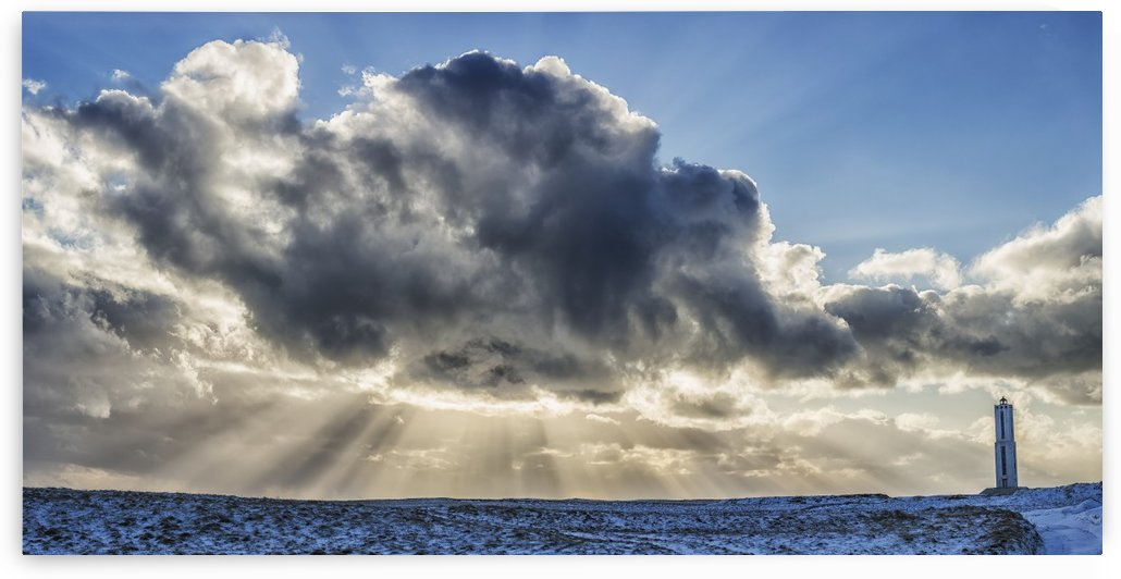 Rays of light shine out from behind the clouds in the skies above a lightnouse along the southern shore of Iceland; Iceland by PacificStock