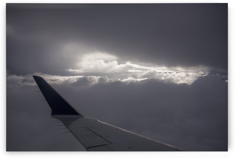 Wing of an airplane with sunlight shining through storm clouds; Astoria, Oregon, United States of America by PacificStock