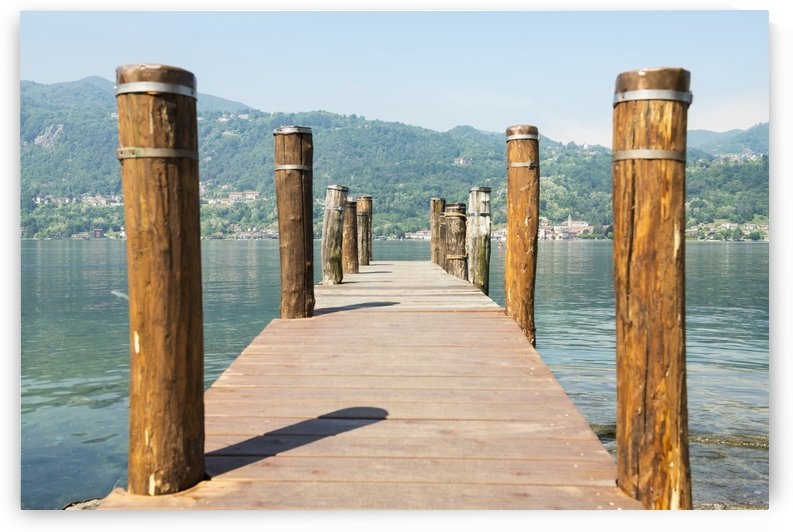 Wooden dock and posts on Lake Orta; Orta, Piedmont, Italy by PacificStock
