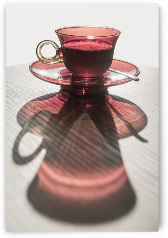 A red glass cup a saucer with a beverage reflected on a white surface; Locarno, Ticino, Switzerland by PacificStock