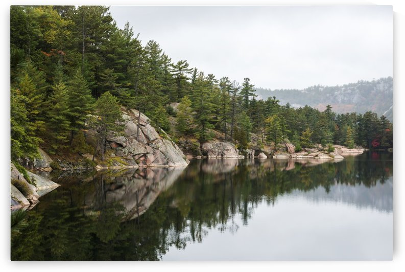 Green coniferous forest on a tranquil lake shore with red rock geological formations; Killarney, Ontario, Canada by PacificStock