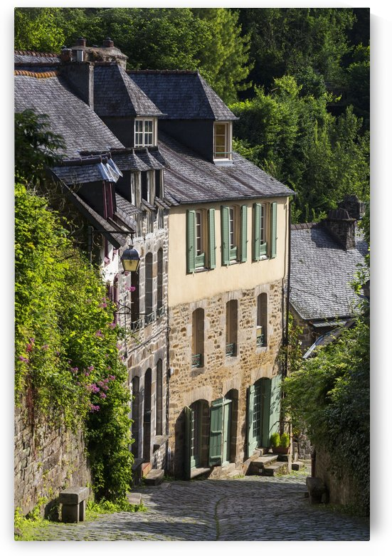 Old stone buildings with green shutters down a cobblestone road; Dinan, Brittany, France by PacificStock