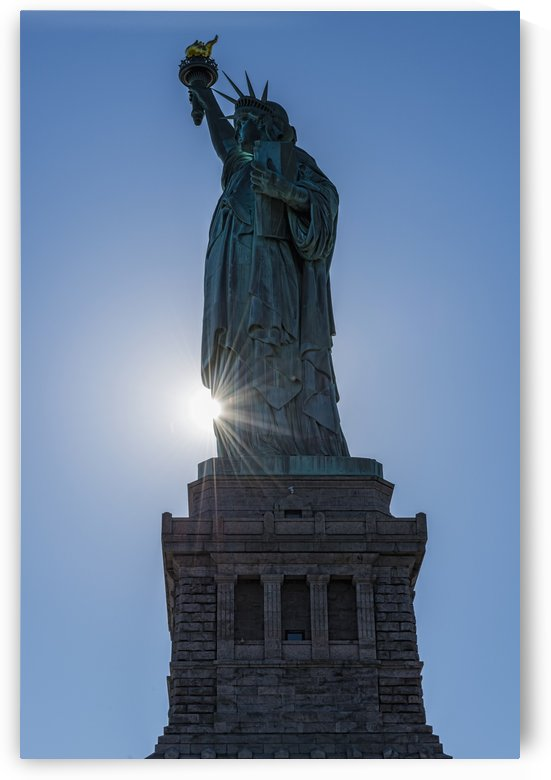 Sun setting behind the Statue of Liberty, Liberty Island; New York City, New York, United States of America by PacificStock