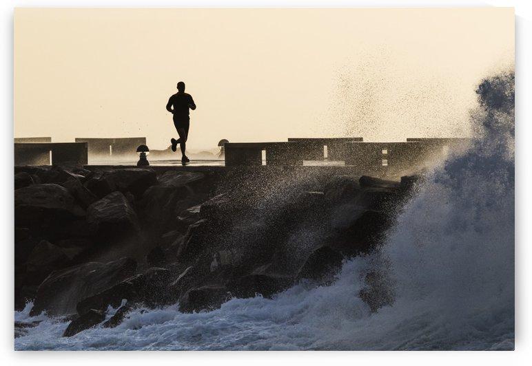 Silhouette of a man running along the coast; La Isla, Tarifa, Cadiz, Andalusia, Spain by PacificStock