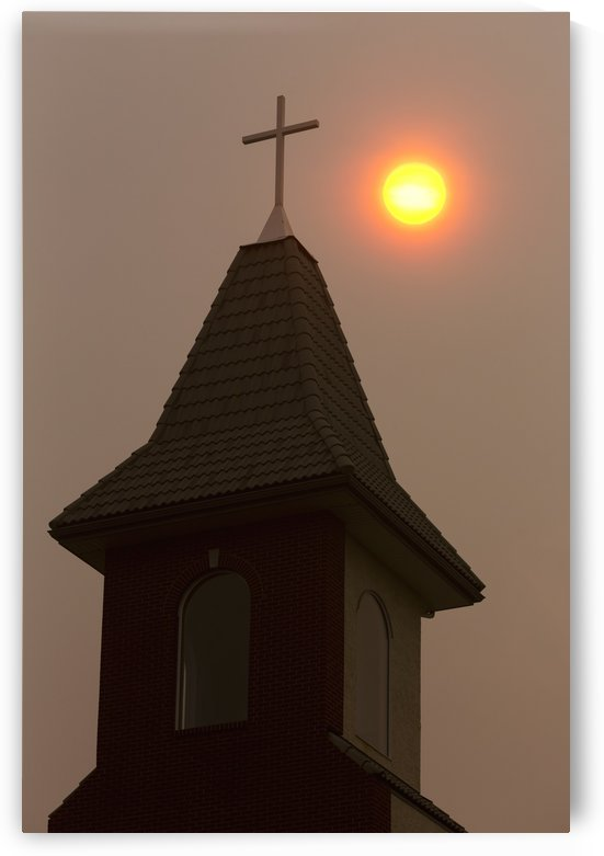 Silhouette of church steeple with orange sun ball in a hazy sky; Calgary, Alberta, Canada by PacificStock