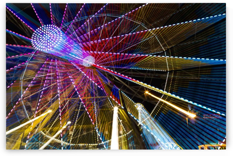Colourful lights of a moving ferris wheel at nighttime; Calgary, Alberta, Canada by PacificStock