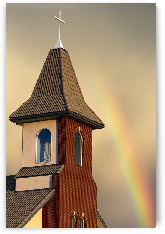 Church steeple with orange glow from the sunset and rainbow in the sky; Calgary, Alberta, Canada by PacificStock