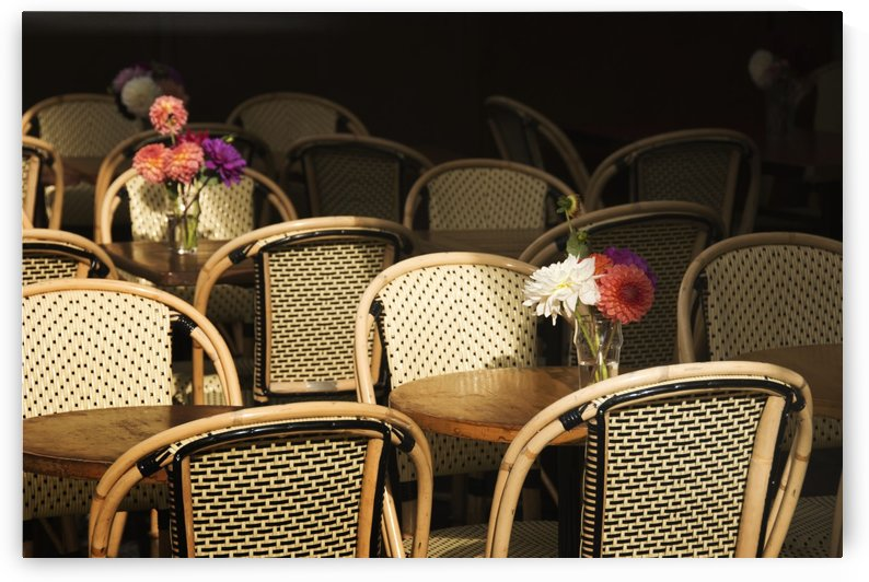 A bouquet of flowers amongst empty parisian bistro chairs and tables; Paris, France by PacificStock