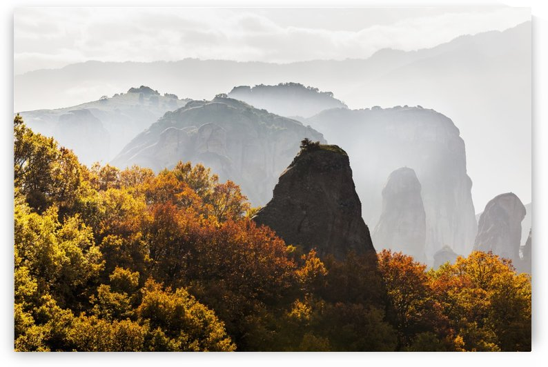 Low cloud around the rugged cliffs with foliage in autumn colours; Meteora, Greece by PacificStock