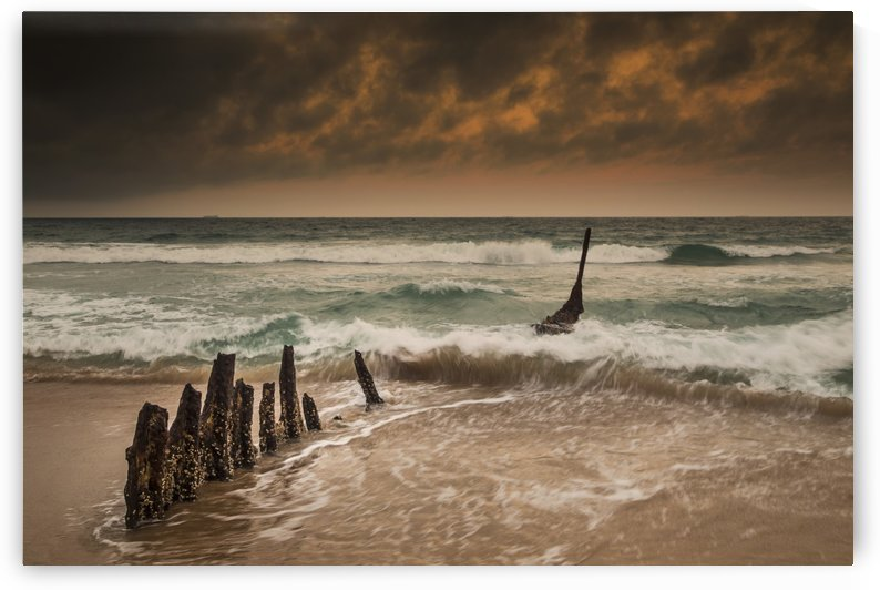 Wooden posts on a beach with a boat being tossed in the water and waves crashing into the sand under a cloudy sky; Queensland, Australia by PacificStock