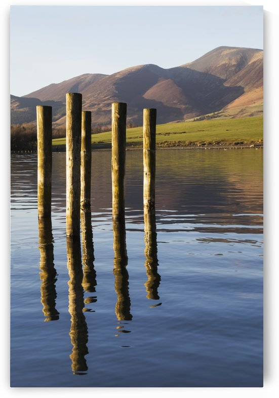 Wooden posts reflected in tranquil after with mountains the the background; Keswick, Cumbria, England by PacificStock