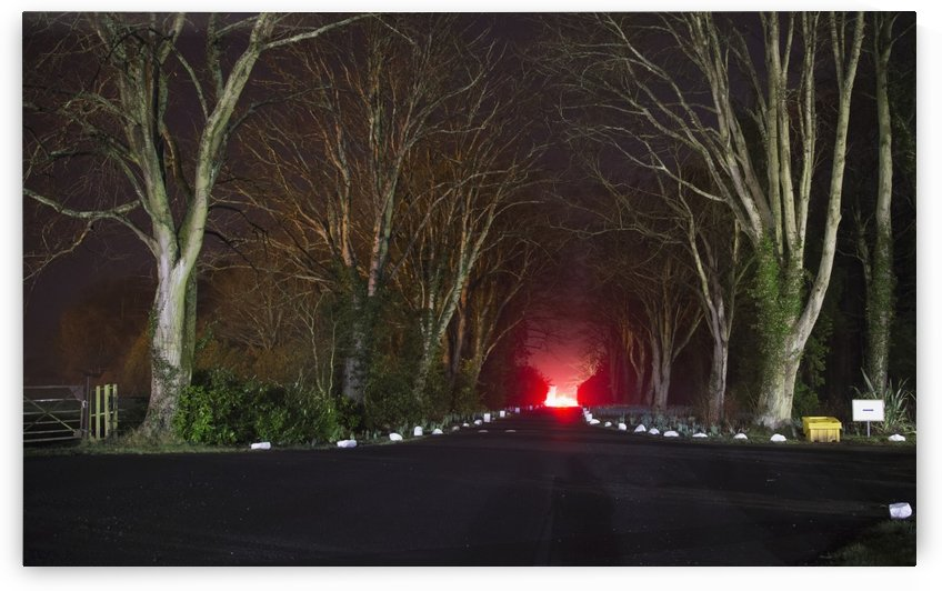 Red light, smoke and flames glowing at the end of a driveway; Doxford, England by PacificStock