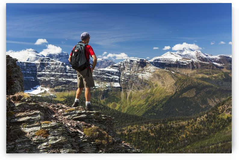 Male hiker standing on top of mountain ridge overlooking snow peaked mountains and forest valley below with blue sky and clouds; Waterton, Alberta, Canada by PacificStock