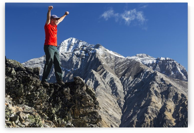 Male hiker standing with arms raised in the air on top of mountain ridge overlooking snow peaked mountains with blue sky and clouds, Kananaskis Provincial Park; Alberta, Canada by PacificStock