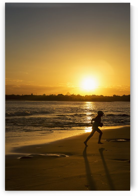 Silhouette of a child running on a beach at sunset; Caloundra, Queensland, Australia by PacificStock
